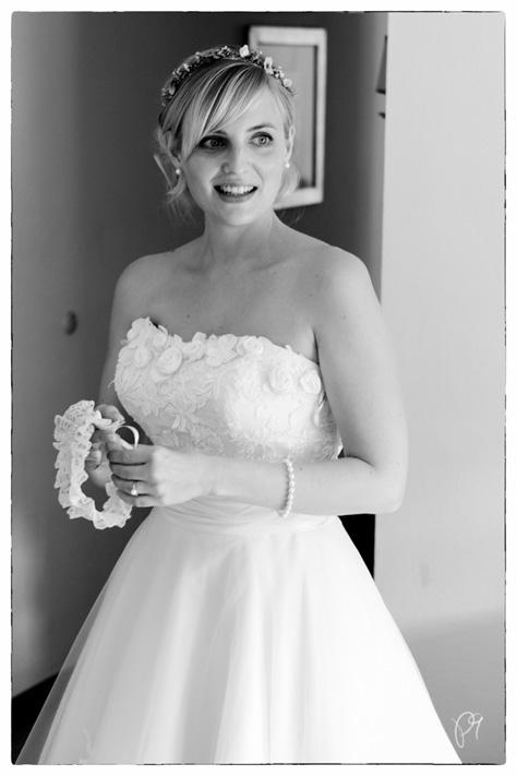 Braut bei Hochzeitsvorbereitungen. Sie hält einen Strumpfband.