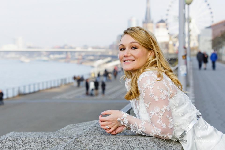 Portrait einer Braut, die sich auf ein Gelände stützt. Im Hintergrund sieht man die Rheinschleife von Düsseldorf.