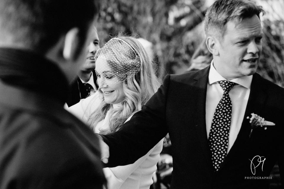Ein Brautpaar im nach der Trauzeremonie im Standesamt Inselstr. Düsseldorf. Dieses schwarzweiss Foto ist Teil einer Hochzeitsreportage und wurde im Hofgarten Düsseldorf aufgenommen.